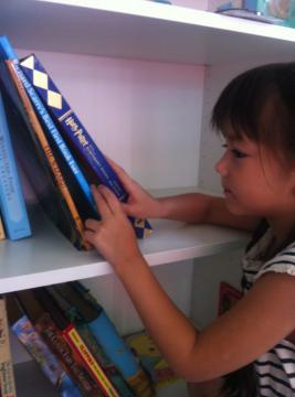 Ella picking out a book at 語言家 Language Plus Living Space